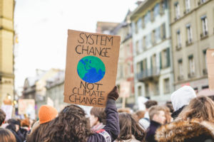 """Blick in eine Demonstrantenmenge. Eine Mädchen hält ein Schild in die Höhe auf dem steht """"System change - not climate change"""""""