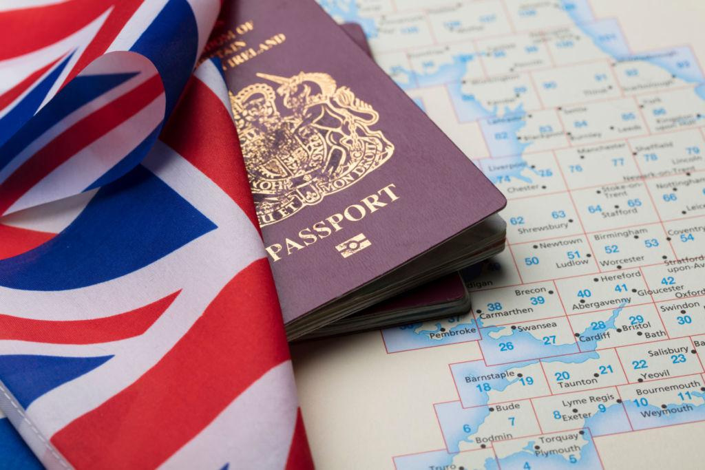 Ein britischer Reisepass, eine Union Jack-Flagge und eine Landkarte von Großbritannien