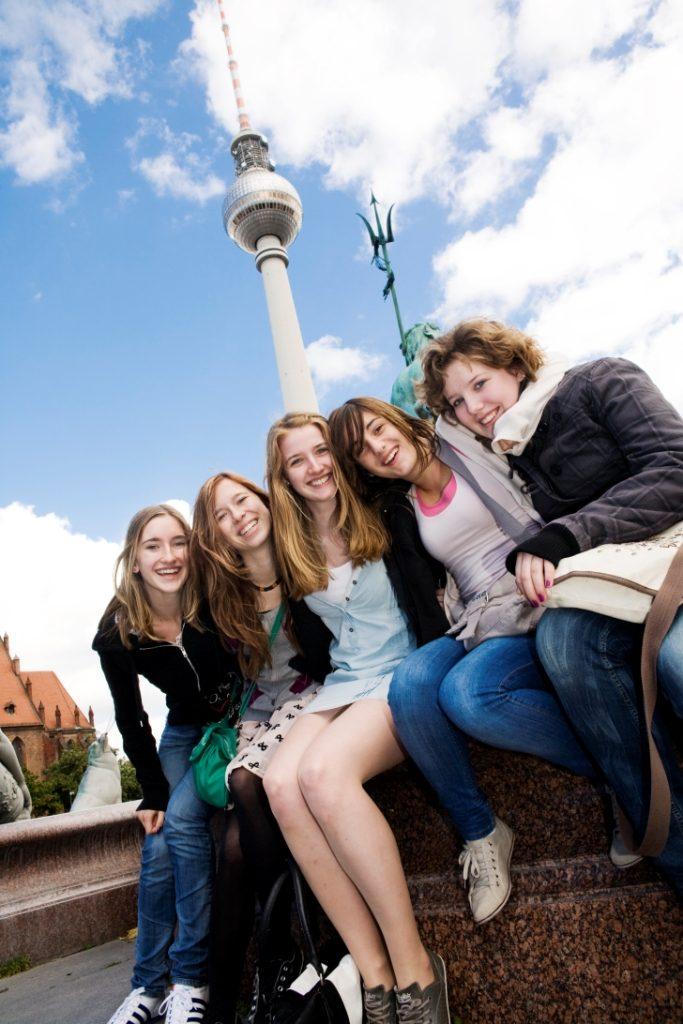 Schülerinnen sitzen auf Klassenfahrt vor dem Fernsehturm in Berlin