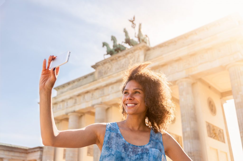 Mädchen macht ein Selfie vor dem Brandenburger Tor in Berlin