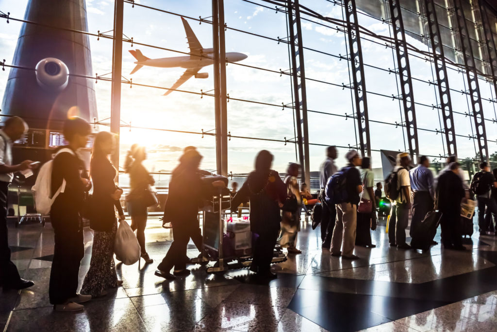 Ein Flugzeug startet an einem Flughafen, im Vordegrund warten Reisende am Check-In Schalter.