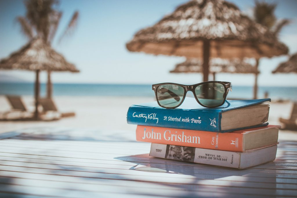 Blick auf einen STabel Bücher am Strand