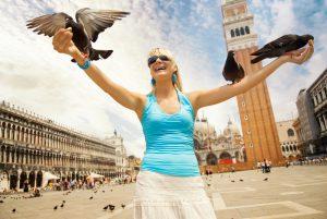 Blick auf eine Frau, die auf einem Marktplatz Tauben füttert