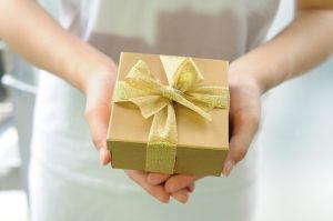 Eine Frau hält ein Geschenk mit einer gelben Schleife in den Händen und zeigt es in die Kamera.