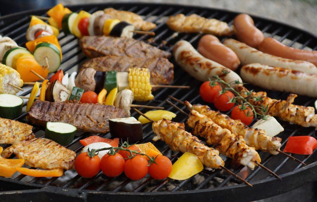 Blick auf einen Grill, der mit Fleisch und Gemüse bestückt ist