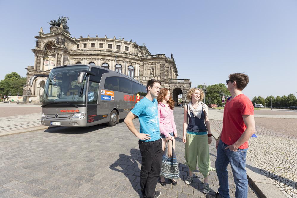 Einige Jugendliche vor einem firmeneigenen Bus