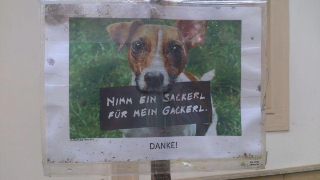 """Hinweisschild, auf dem ein Hund mit einem Schild im Maul zu sehen ist. Auf dem Schild steht: """"Nimm ein Sackerl für mein Gackerl."""""""
