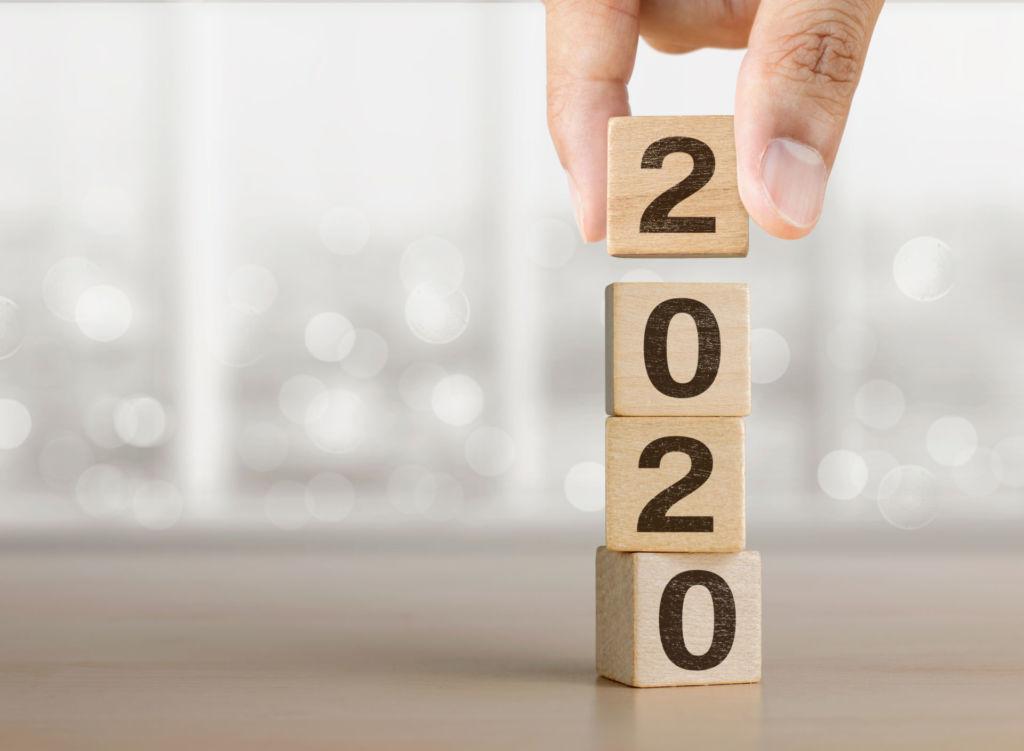 Holzwürfel mit den Jahreszahlen 2020 werden aufeinandergestapelt.