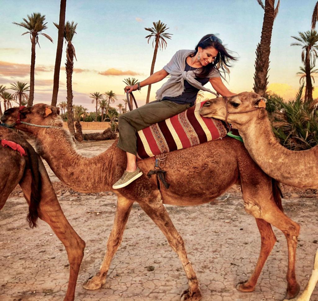Eine junge Frau sitzt lächelnd auf einem Kamel.