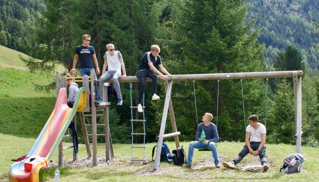 Blick auf Schüler, die in Tirol auf einem Klettergerüst sitzen