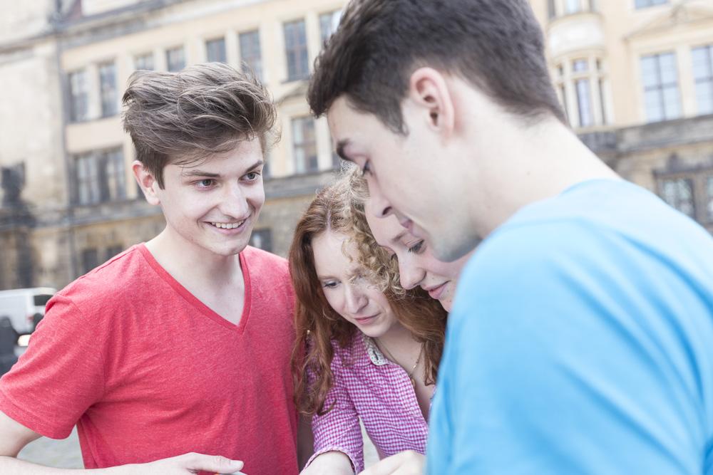 Jugendgruppe betrachtet einen klinen Gegenstand