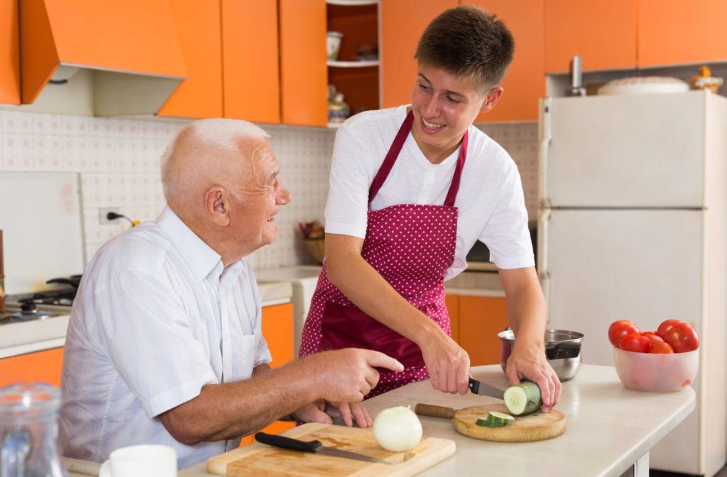 Jugendlicher kocht mit einem alten Mann im Altersheim