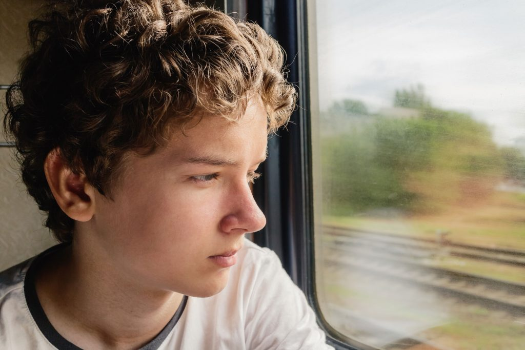 Ein Junge sitzt alleine im Zug und schaut aus dem Fenster