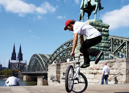 Blick auf einen jungen Mann, der mit einem BMX Kunststücke in Köln macht