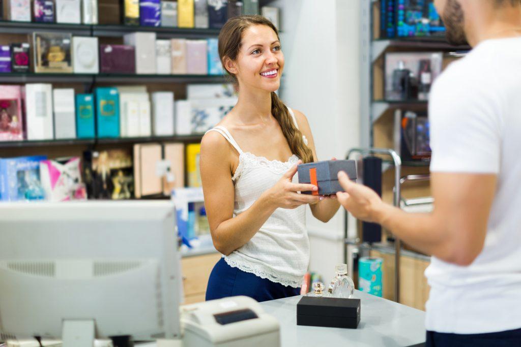 Blick auf eine Auszubildene, die einem Kunden Ware überreicht