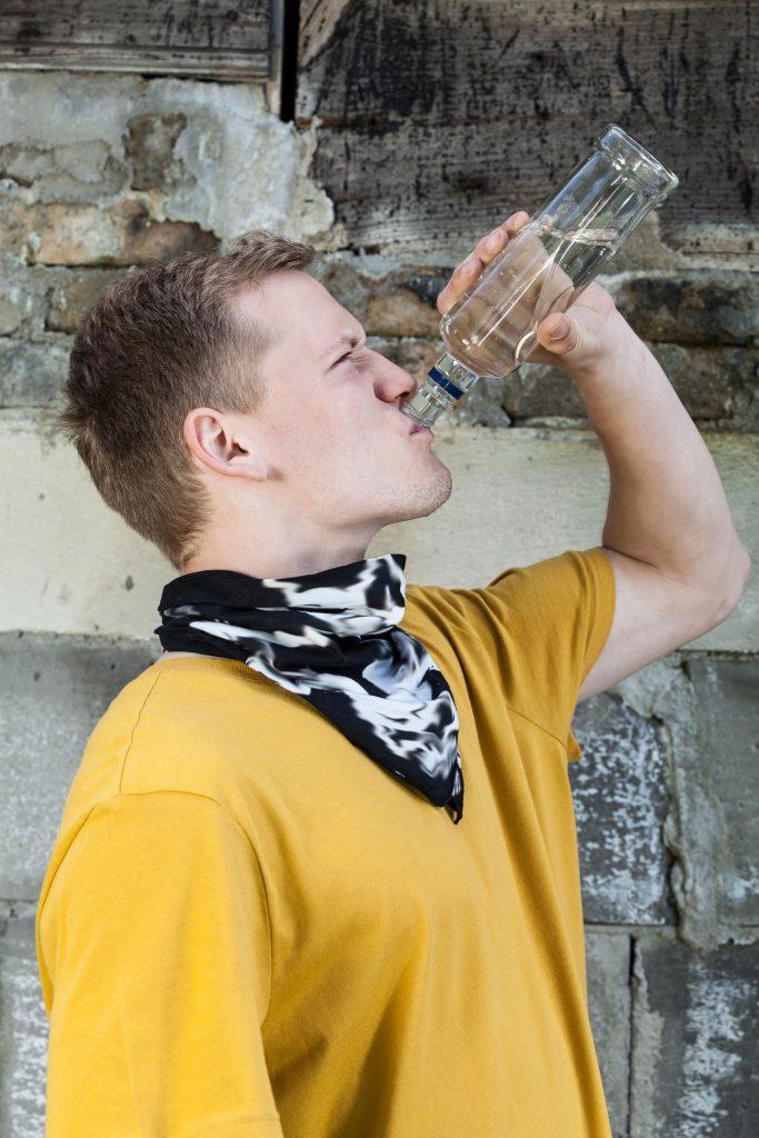 Junge hält eine Flasche mit Alkohol in der Hand und trinkt diesen