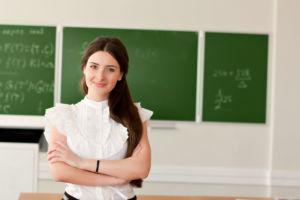 Junge Lehrerin vor einer Tafel