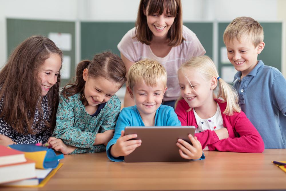 Blick auf eine Schülergruppe, die ein Tablet bedient