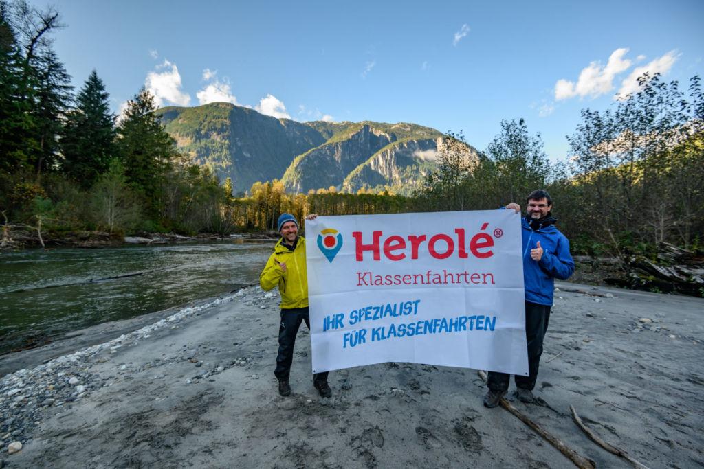 Geschäftsführer Carsten Herold von HEROLÉ Reisen und Kai Andersch von Wilderness International halten ein HEROLÉ-Plakat in den Händen.