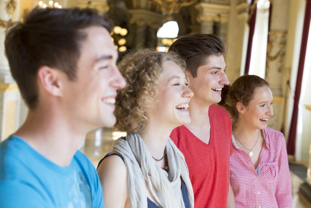 Lachende Schülergruppe schaut aus einem Fenster