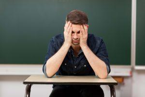 Blick auf einen Lehrer, der die Arme vor dem Kopf verschränkt