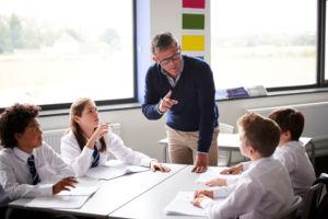 Ein Lehrer erklärt vier Schülern einen Sachverhalt im Rahmen einer Gruppenarbeit (© Shutterstock Bild-ID: 1195671607)