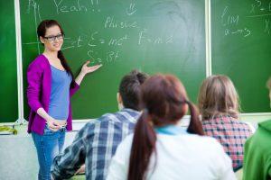 Lehrerin steht an einer Tafel vor ihrer Klasse