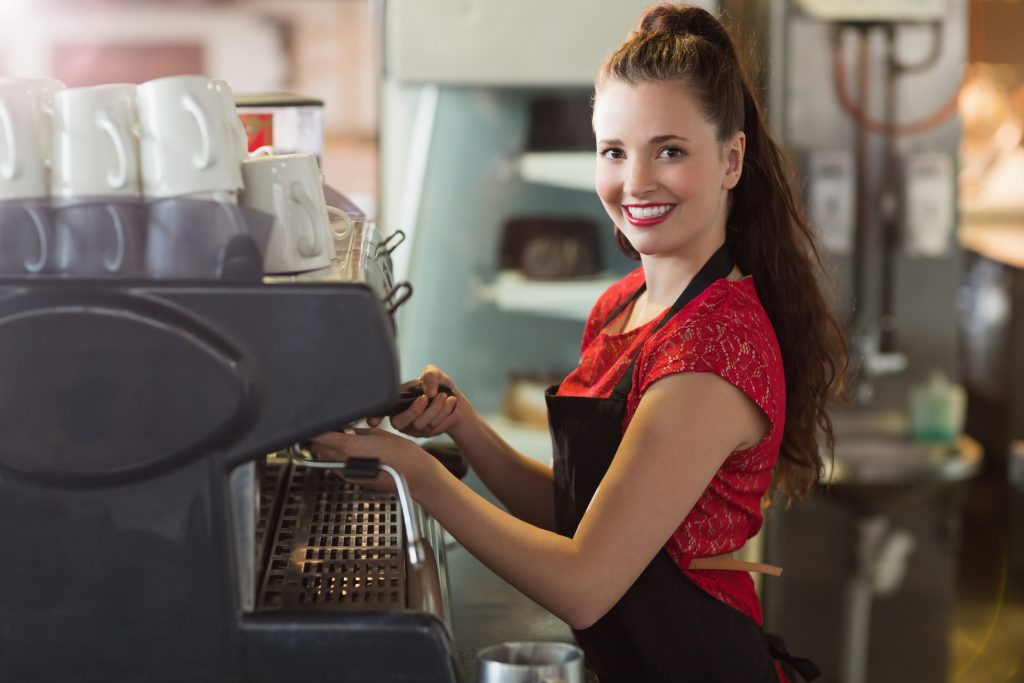 Blick auf ein Mädchen, das eine Kaffeemaschine bedient