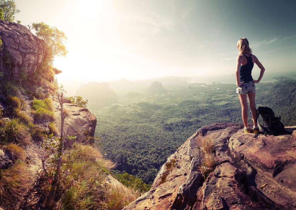 Jugendliche steht auf einem Felsen und blickt über eine einzigartige Landschaft