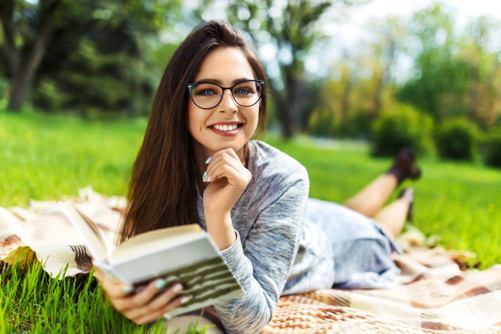Blick auf ein Mädchen, was auf einer Decke liegt un ein Buch liest