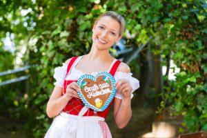 Mädchen hält ein typisch bayrisches Lebkuchenherz mit Aufschrift in der Hand