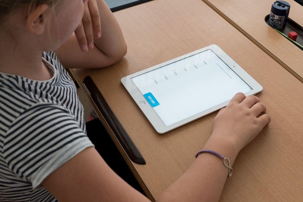 Mädchen sitzt vor einem Tablet und nimmt an einer Abstimmung teil
