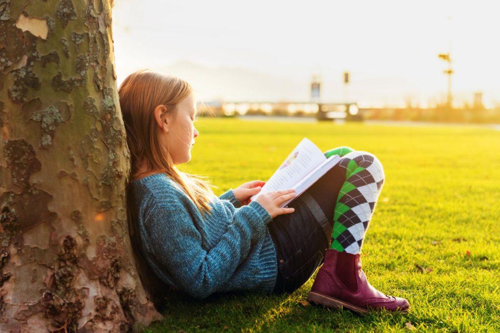 Mädchen sitzt vor einem Baum und liest