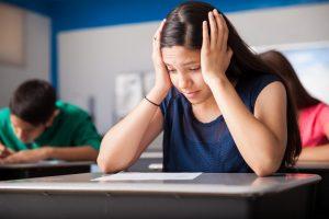 Mädchen sitzt betrübt einem Arbeitsblatt