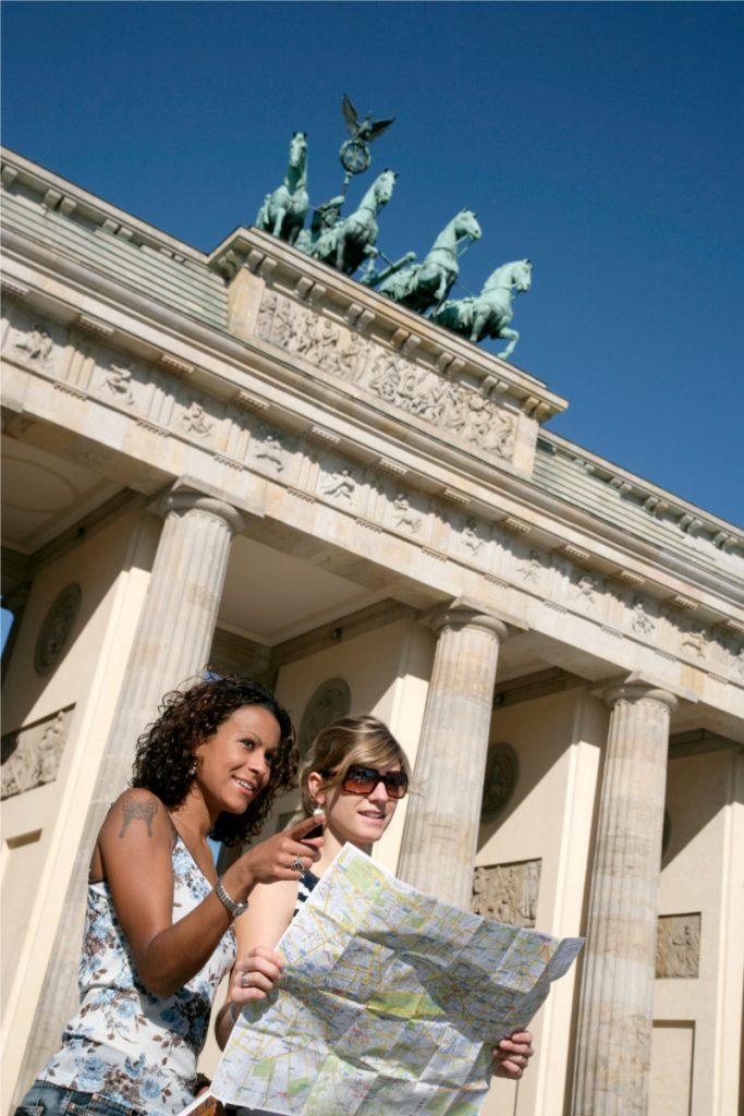 Mädchen stehen mit einerm Stadtplan in der Hand vor dem Brandenburger Tor in Berlin