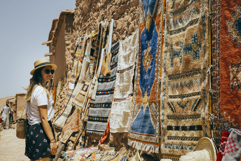 Eine junge Frau auf einem Markt in Marrakesch sieht sich orientalische Teppiche an.