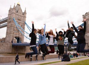 Mädchengruppe springt vor der Tower Bridge in London in die Luft