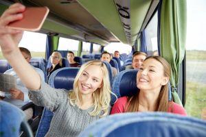 Mädchen in einem Reisbus, die ein Selfie machen