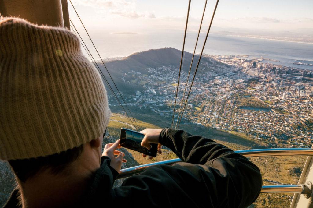 Mann macht ein Foto aus einer Gondel vom Mountain Cableway