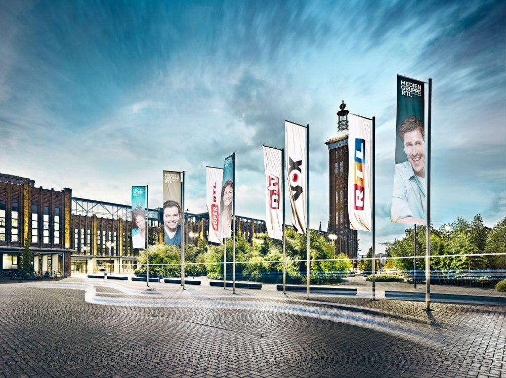 Fahnen vor dem Hauptgebäude der Mediengruppe RTL Deutschland in Köln