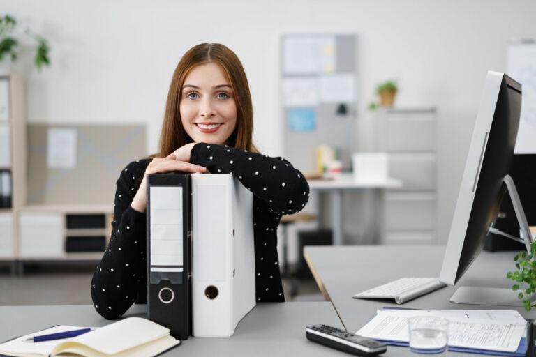 Eine Mutter sitzt zu Hause am Schreibtisch vor ihren Aktenordnern und vor dem Computer. Wie Sie Eltern von einer Klassenfahrt begeistern können, erfahren Sie im HEROLÉ Ratgeber.