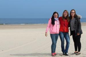 Drei Reiseexpertinnen posieren für ein Foto am Strand.