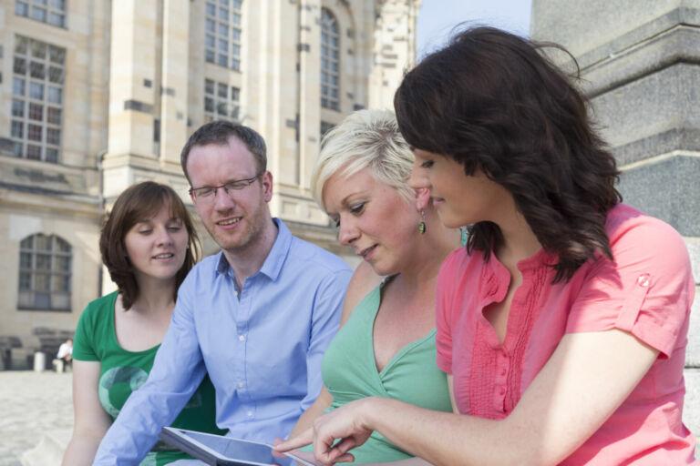 Eine Reisegruppe erkundigt sich über ein Tablet auf dem Altmarkt in Dresden über Ausflugsziele