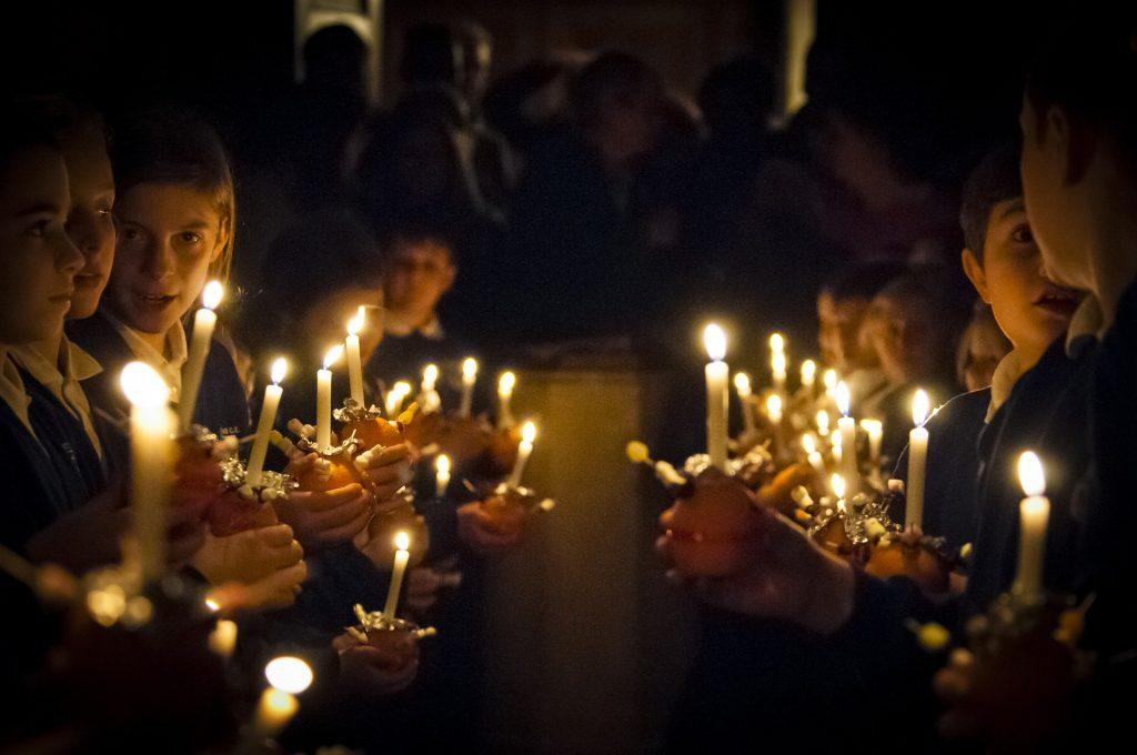 Schülergruppe beim Kerzen anzünden zu Weihnachten