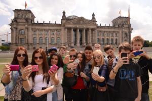 Eine Schülergruppe auf Klassenfahrt vor dem Bundestag in Berlin ein Selfie.