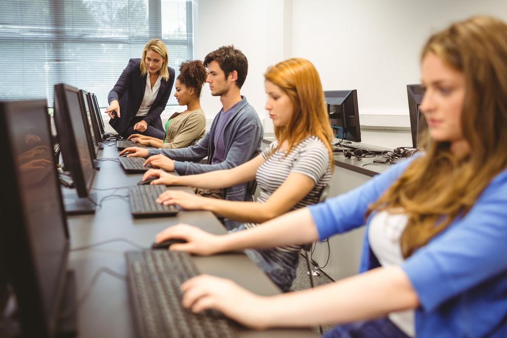 Blicka uf Schüler, die im Computer-Kabinett arbeiten