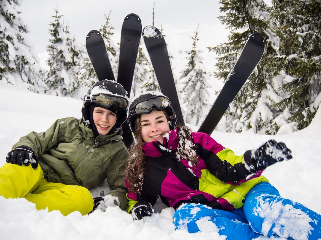 Blick auf zwei Schüler, die fröhlich im Schnee sitzen