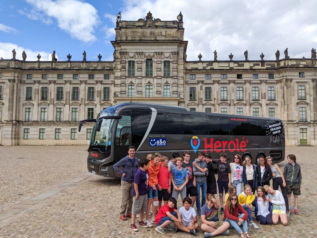 Portrait einer Schülergruppe auf Klassenfahrt vor einem Reisebus von HEROLÉ