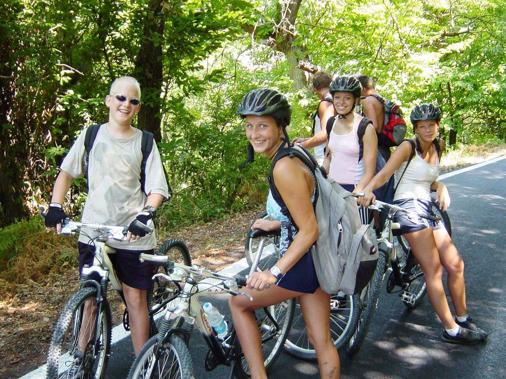 Eine lachende Schülergruppe bei einer kleinen Pause während des Fahrradfahrens