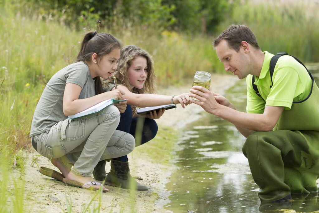 Zwei Schülerinnen unternehmen mit Ihrem Biologielehrer eine Exkursion und untersuchen Wasserproben